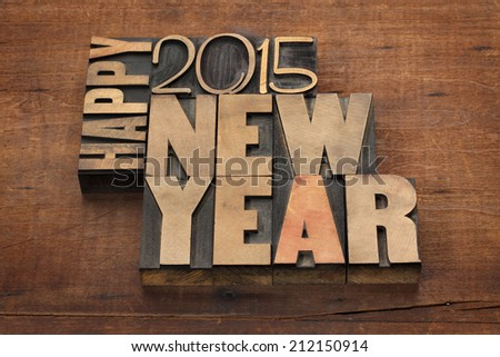 Happy New Year 2015 greetings - text in vintage letterpress wood type blocks on a grunge wooden background - stock photo