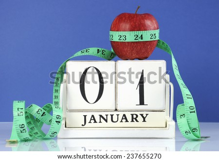Happy New Year healthy slimming weight loss or good health resolution with red apple and measuring tape on white wood vintage style calendar for January first. - stock photo