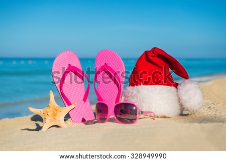 Happy  New Year holidays and Merry Christmas at Sea. Sandals, sunglasses and santa hat on sandy beach. - stock photo