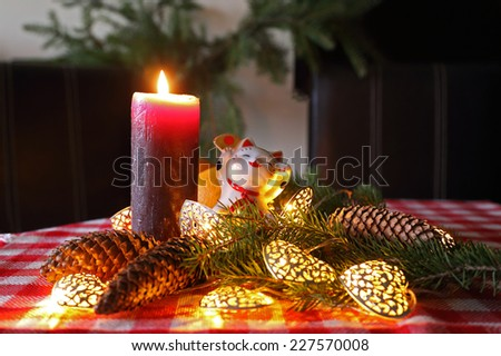 Happy New Year home decoration with maneki-neko, candle and christmas tree on the dinner table. - stock photo