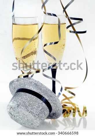Happy New Year image includes two flutes of bubbly champagne, a silver sparkle top hat and swirls of silver and gold curly ribbon cascading from above on a reflective surface with a bright background. - stock photo