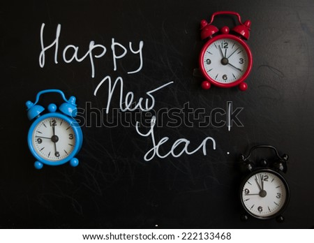 happy new year is written on a blackboard and old-styled clocks