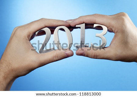 Happy New Year 2013. Man holding metallic numbers 2013 in his hands. - stock photo