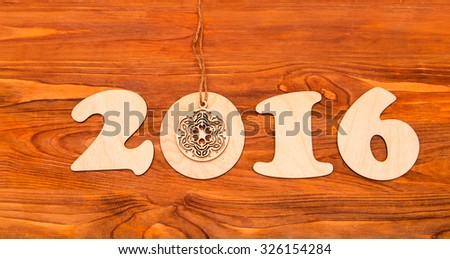 Happy New Year 2016 number made of wood and carved by snowflake