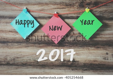 Happy new year 2017 on colorful paper with clothespin hanging on a string with wooden background, retro style - stock photo