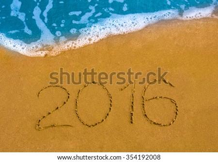Happy New Year 2016 on the sea beach. - stock photo