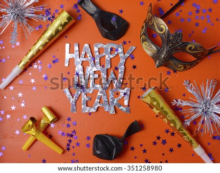 Happy New Year Party Decorations on festive orange wood table.