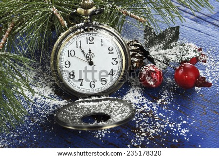 Happy New Year pocket fob watch with five to midnight time and decorations on dark blue rustic distressed vintage wood. - stock photo