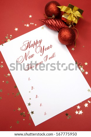 Happy New Year resolutions writing on notepad paper, This year I will, list of goals against a red background with festive decorations. - stock photo