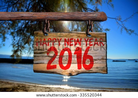 Happy new year 2016 sign on old wood with blurred background