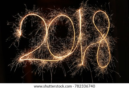 Happy new year 2018 text written with Sparkle fireworks isolated on black background