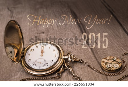 Happy New Year 2015! Vintage watch on a wooden background showing five to twelve. - stock photo