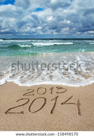Happy New Year 2014 wash away year 2013 concept on sea sand beach - stock photo