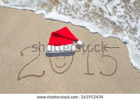 happy new year 2015 with smiley face in santa hat on sandy beach with wave - christmas holiday concept - stock photo