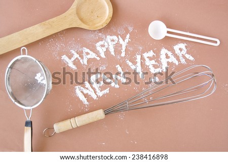 happy new year wording make with flour with kitchen utensil on background - stock photo