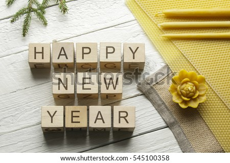 Happy New Year words on cubes on a white wooden background
