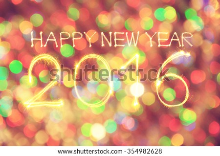 Happy New Year 2016 write sparkler with Defocused light blur bokeh background in Vintage tone
