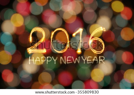 Happy New year 2016 written by sparklers firework with blurred colorful and gold lights bokeh background - stock photo