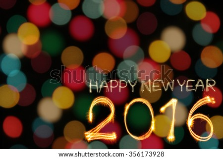 Happy New year 2016 written by sparklers firework with blurred colorful gold lights bokeh background - stock photo