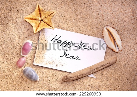 Happy new year, written on a note in the sand with seashells - stock photo