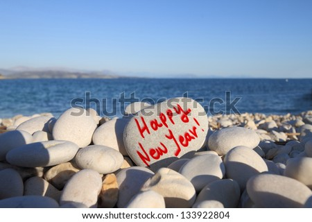 Happy new year written on heart shaped stone on the beach with spray brush - stock photo