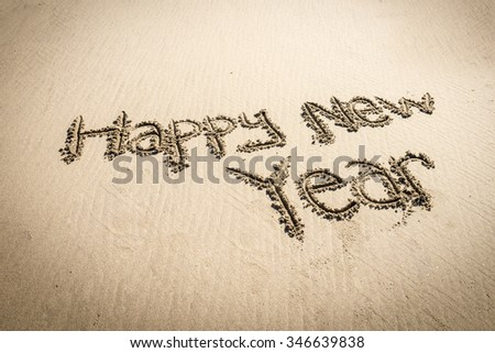 Happy new year written on sand - stock photo