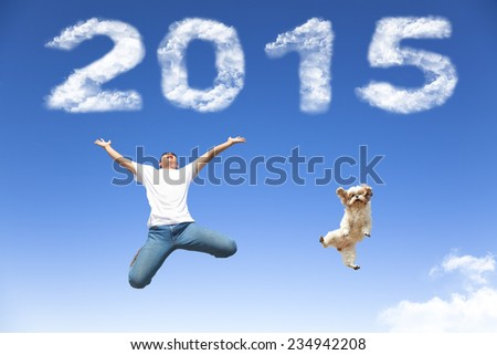 happy new year 2015.young man and dog  jumping together with blue sky background - stock photo