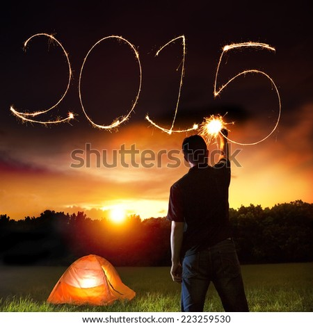 happy new year 2015. young man drawing 2015 by sparkling stick. camping on the mountain - stock photo