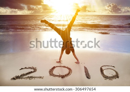 happy new year 2016. young man handstand on the beach - stock photo