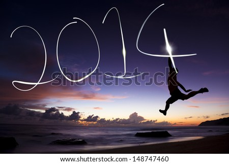 happy new year 2014.young man jumping and drawing 2014 by flashlight - stock photo