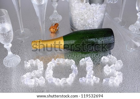 Happy New Years. 2013 spelled out with ice cubes on a wet metallic surface, surrounded by a champagne bottle, and flutes. - stock photo