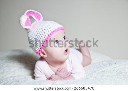 Happy newborn baby dressed in Easter bunnies - stock photo