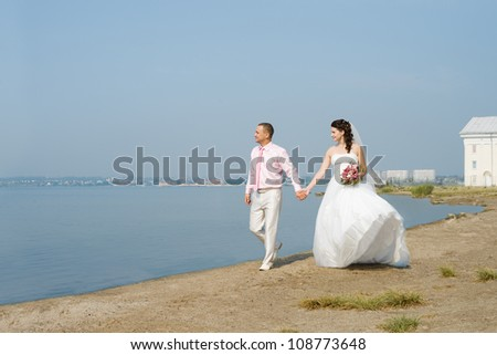 happy newly married couple in white dress, romance walk to  sea beach