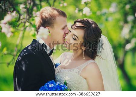 happy newly married couple is standing in a branches of blooming cherry tree in sunny spring day, groom is kissing his beautiful bride in a gorgeous wedding dress in her cheek