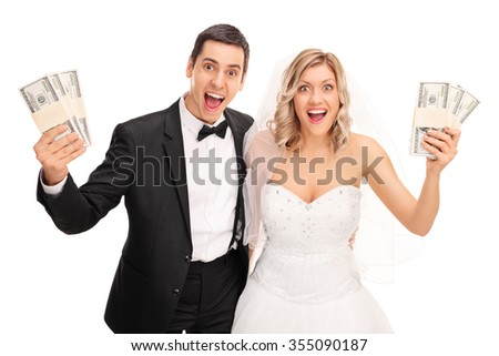 Happy newlywed couple holding few stacks of money and looking at the camera isolated on white background