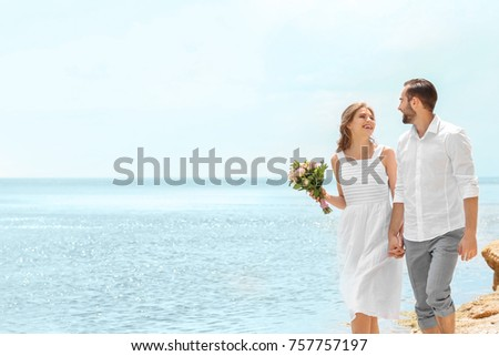 Happy newlywed couple walking on seashore