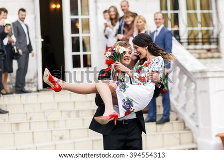 Happy newlywed groom carrying beautiful ukrainian bride out of registry