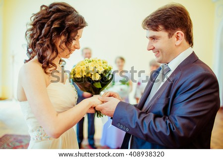 Happy newlywed romantic couple exchanging wedding rings on ceremony - stock photo