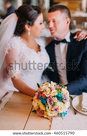 Happy newlyweds embracing and dreaming of their new married life in restaurant hall at the table