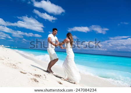 Happy newlyweds in white dresses having fun on beach with  turquoise sea background