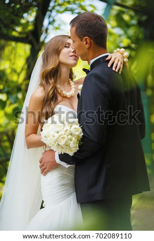 Happy newlyweds kiss and hug