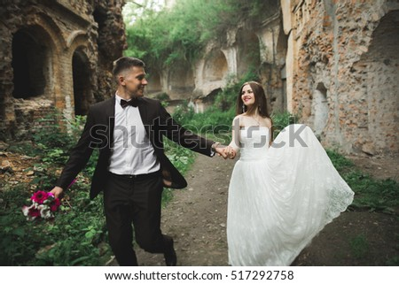 Happy newlyweds near the ancient castle on the walk