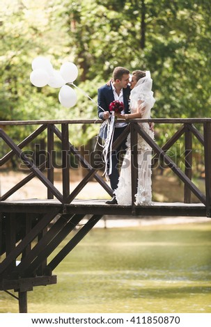 Happy newlyweds posing on wooden bridge across river with balloons - stock photo