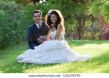 Happy Newlyweds sitting in green park at sunset - stock photo