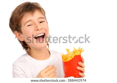 Happy nine year old boy eating french fries and laughing. Fast food. Concept of healthy and unhealthy food. Isolated over white. - stock photo