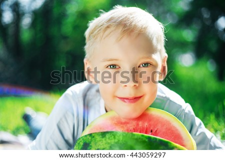 happy nine years old boy eating watermelon in the park