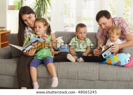 Happy nuclear family with three children having fun sitting on sofa at home, reading books, smiling. - stock photo