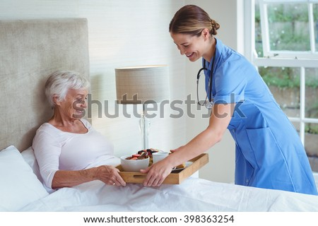 Happy nurse giving food to senior woman at home - stock photo