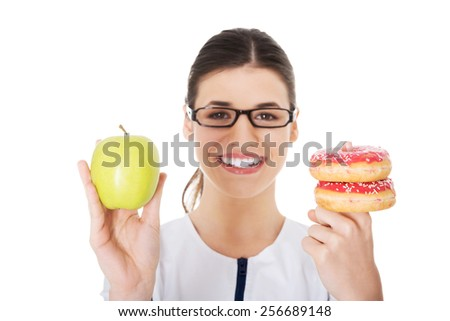 Happy nutritionist holding a cake and apple - stock photo