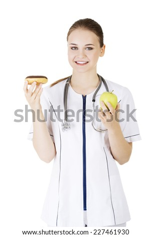Happy nutritionist holding a donut and apple - stock photo